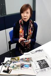 フェイスブックを更新するスマートフォンを手に、震災や亡き母について語る村田美弥子さん=神戸市中央区東川崎町1