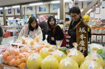 道の駅坂本でバンペイユや地元産の野菜を見る留学生たち=八代市
