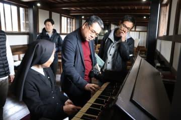 ド・ロ神父が実際に使用したオルガンを弾いてみる記者ら=長崎市、旧出津救助院