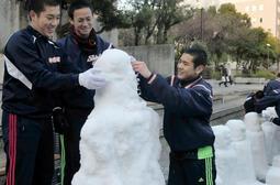 雪地蔵づくりに励む神港学園高校の硬式野球部員ら=16日午後、東遊園地