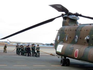 【輸送ヘリを引く新成人の隊員ら=伊勢市小俣町明野の陸自明野駐屯地で】