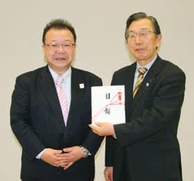桜井会長(左)から寄贈物品目録を贈られ笑顔を見せる市社会福祉協議会の柳谷会長
