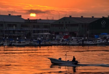 美しい夕焼けが、漁船の浮かぶ水面をあかね色に染めている=船橋市