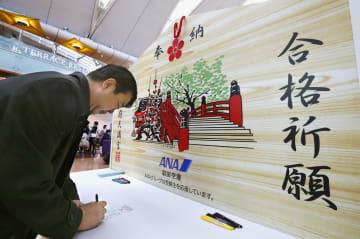 羽田空港に登場した太宰府天満宮の特大絵馬。子どもの大学合格を祈る男性が「願い札」に記入していた=17日午前