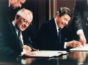 1987年12月、ホワイトハウスでINF全廃条約に調印するレーガン大統領(右)とゴルバチョフ・ソ連書記長(ロイター=共同)
