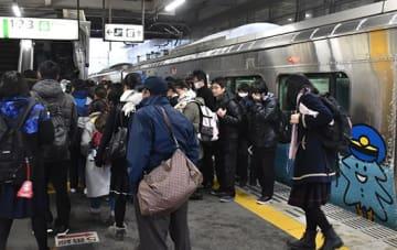 八戸駅に到着、混雑した車両から降りて足早にエスカレーターに向かう高校生たち=17日午前7時9分