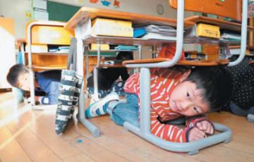 訓練で椅子の下に隠れる児童=17日午前、大分市の鶴崎小