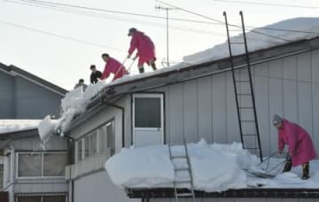 雪下ろしをする「夢雪隊」のメンバー=12日、十日町市山野田