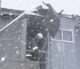 強風で剥がれた屋根を固定する消防隊員=17日午後2時10分、室蘭市日の出町