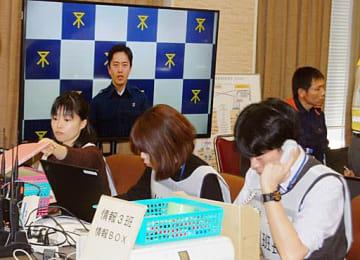吉村市長による「災害モード宣言」の映像を前に情報収集に当たる職員ら=17日、大阪市役所