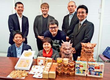 那覇土産として「龍柱会議」のブランドで展開する土産品の一部と開発したメーカーの代表者ら=17日、沖縄タイムス社