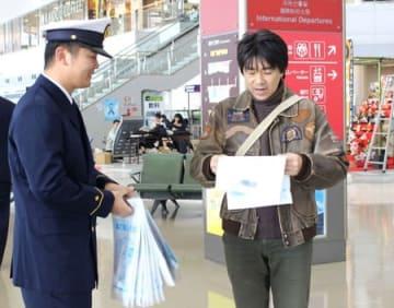 チラシやグッズを配って118番をPRする海上保安官=18日、新潟市東区の新潟空港