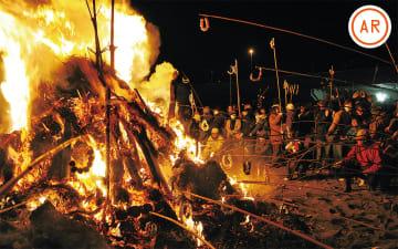 燃え盛る炎に団子を括り付けた竹竿を伸ばす参加者