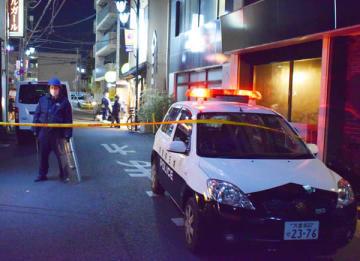 男性2人が刺された殺人未遂事件で、規制線が張られ、現場のビルに出入りする警察官ら=18日午後7時ごろ、さいたま市大宮区宮町