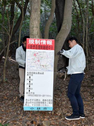 大幡山から獅子戸岳までの登山道が通行可能になったことを伝える看板を設置する小林市職員=18日午前、小林市南西方