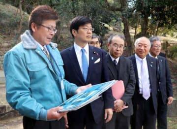 大島大橋を望む高台で橋の復旧状況を聞く阿達政務官(左から2人目)