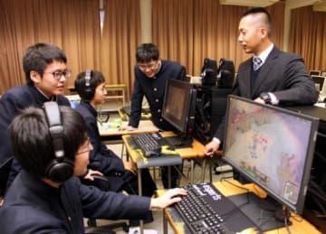 パソコンを見ながらゲームの戦略を立てる生徒たち。右端は湯浅教諭