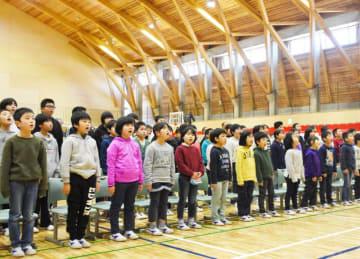 地元木材を多く使った体育館で校歌を合唱する気仙小児童