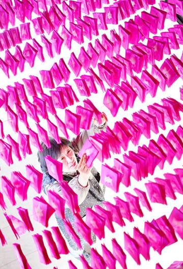 美濃まつりを前にピンク色に染めた和紙を干す後藤早智子さん=18日午後2時24分、美濃市上条、双葉紙業