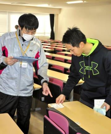 試験会場の教室の机に受験番号などを記したシールを貼る職員=18日午前、松山市文京町の愛媛大