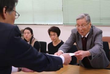 被爆者健康手帳の早期交付を求める要望書を中川部長(左)に手渡す月川共同代表=長崎市役所