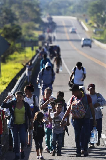 18日、米国境を目指しメキシコ南部タパチュラを歩く、中米ホンジュラスからの移民ら(AP=共同)