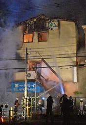 燃える店舗兼住宅に放水する消防隊員ら=19日午前3時26分、兵庫県宝塚市中野町