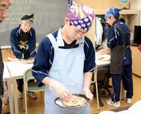 ピザ生地に思い思い好きな具を載せていく生徒
