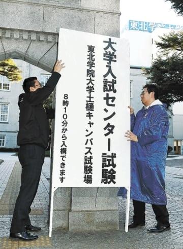試験会場の看板を設置する職員=仙台市青葉区の東北学院大土樋キャンパス