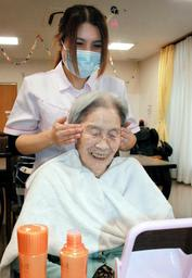 顔のトリートメントを受ける90代の女性。笑みがこぼれる=三田市天神1、サービス付き高齢者向け住宅「和」