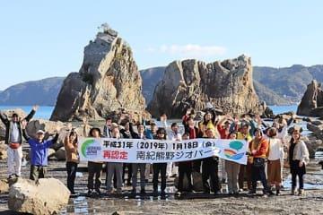 【橋杭岩の前でジオパーク再認定を喜ぶ関係者(18日、和歌山県串本町くじの川で)】