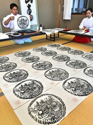 【熊野那智大社の鬼面札を一枚ずつ丁寧に刷る神職(18日、和歌山県那智勝浦町那智山で)】