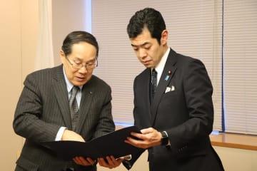 「長崎アピール」を辻政務官(右)に手渡す朝長実行委員長=外務省