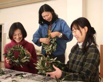 完成したオリーブ冠の出来映えを確認する西村さん(中)たち