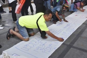 タイのタマサート大で開かれた集会で「総選挙を延期するな」などとメッセージを書く市民ら=19日、バンコク(共同)