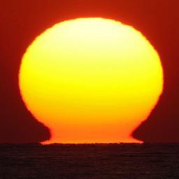 水平線に沈んでいく「だるま夕日」=19日午後5時12~13分、神戸市垂水区東舞子町から南西方向を望む