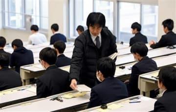 受験生に問題用紙を配布する大学職員=19日午前、熊本市の熊本大(上杉勇太)