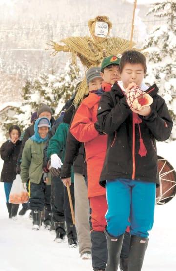 わら人形を担いで雪道を練り歩く白木野集落の人たち