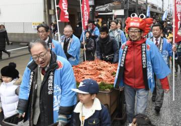 「カニ感謝祭」でベニズワイガニを積み込んだリヤカーとともにパレードする参加者=20日、鳥取県境港市
