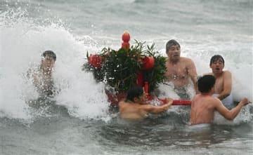 荒波を受けながら、みこしを担いで海を渡る男衆=20日午前、苓北町(上杉勇太)