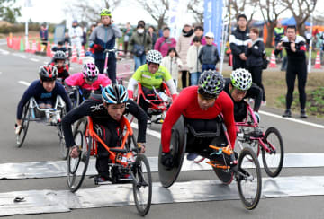 前傾姿勢で一斉にスタートする、競技用車いすの部・10キロの選手ら=20日午後、西都市の西都原古墳群周回特設コース