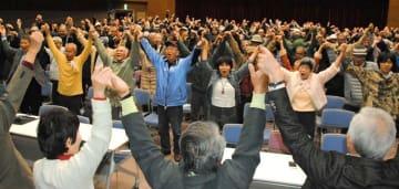 緊急の市民総決起大会を開き、島袋俊夫市長に抗議してガンバロー三唱する参加者=20日午後8時前、うるま市生涯学習文化振興センターゆらてく