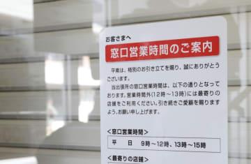 昼休みに入り店舗のシャッターを閉めた、愛知県設楽町の三菱UFJ銀行田口特別出張所に張られた窓口営業時間の案内=21日午後