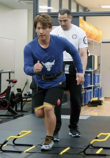 室伏広治氏から体幹トレーニングの指導を受けるオリックス・吉田正=東京都内