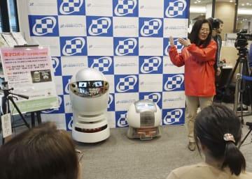 患者を前に漫才を披露した漫才ロボット「あいちゃん」(左)、「ゴン太」と、解説する甲南大知能情報学部の灘本明代教授=21日午後、大阪市の大阪国際がんセンター