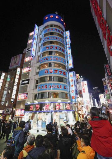 東京都新宿区歌舞伎町のカラオケ店前に集まる報道関係者ら=21日夜