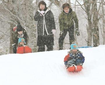 急斜面の雪の滑り台で遊ぶ家族連れ
