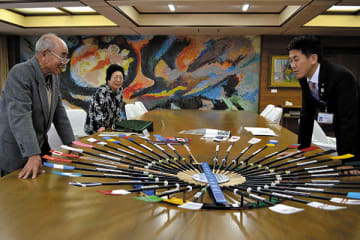 オールのミニチュアを前に語り合う(左から)別府克己さん、ヒロ子さん、菅原文仁市長=戸田市役所
