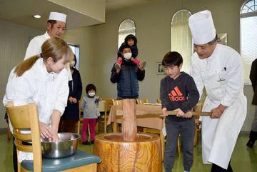 きねを振るって餅つきを体験する子どもら=20日午後、秩父市大宮の道の駅ちちぶ秩父食堂