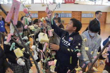 「まゆ玉つくり会」で、桜の木に餅を付ける児童=東海村照沼